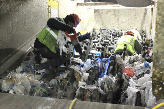 Workers clearing plastic bags in MRF; photo credit DNAinfo Patty Welti